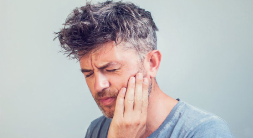 man holding his jaw in pain needs a dental crown