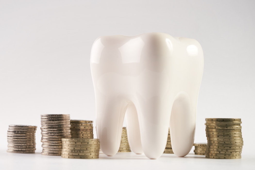 A model of a tooth with stacks of coins surrounding it indicating financial choices related to dental care.
