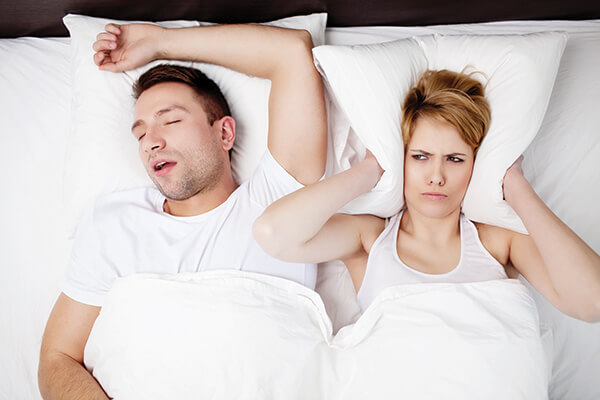 The wife covers her ears with a pillow while the husband snores in her sleep