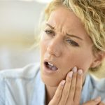 A blonde woman holds her jaw in pain.