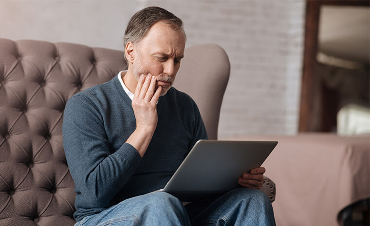 man holding his jaw in pain while looking at his computer