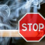 Stop sign superimposed over a smoking cigarette.