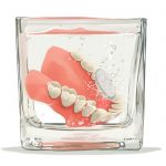 Dentures soaking in a jar with a cleaning tablet.